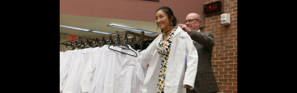 Lawrence Marnett, Ph.D., helps Yan Yan, a new graduate student in the Biological Sciences from China, with her personalized lab coat during last week's Simple Beginnings ceremony for new graduate students. (photo by Anne Rayner)